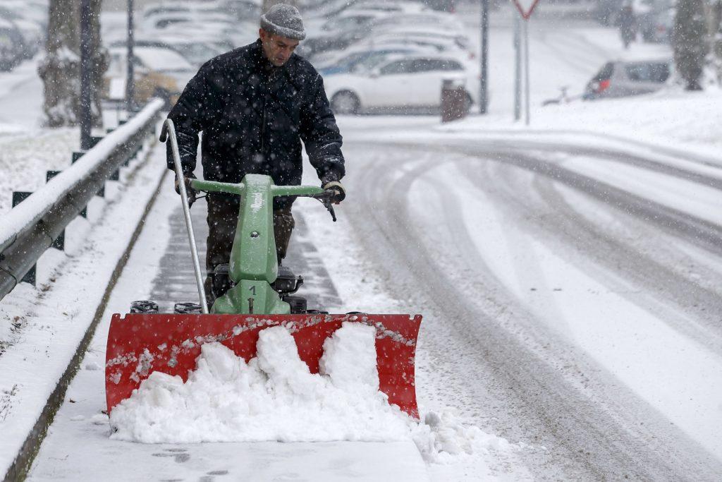 Genf, 2017. január 10. Egy férfi takarítja a havat egy úttest szélén Genfben 2017. január 10-én. (MTI/AP/Salvatore Di Nolfi)