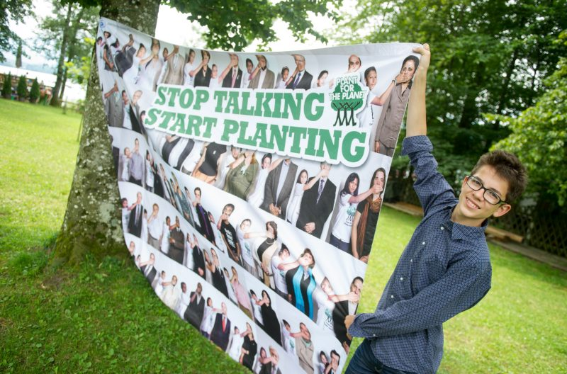The founder of the environmental organisation and action group 'Plant for the Planet',  Felix Finkbeiner, holds a banner in his hands which reads 'Stop Talking Start Planting' as part of his enviornmental campaign in Uffing, Germany, 26 July 2014. Apart from Finkbeiner's committment 'Plant for the Planet' which encourages children around the world to plant tree for environmental protection, he is also committed to putting through the right to vote for minors in Germany. Photo: 26 July 2014. Photo: Tobias Hase/dpa