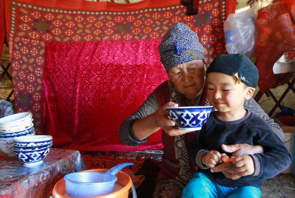 Biskek, 2017. július 13. Egy kirgiz asszony frissen erjesztett kancatejet, kumiszt itat unokájával a kirgiz fõvárostól, Biskektõl 250 km-re délre, a 3000 méter tengerszint feletti magasságban fekvõ Szuszamir-völgyben lévõ nomád táborban 2017. július 11-én. (MTI/EPA/Igor Kovalenko)