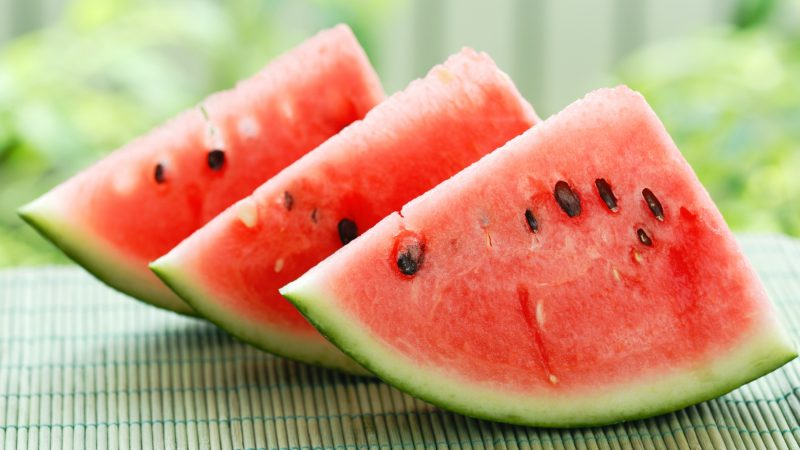 three slices of watermelon on bamboo mat
