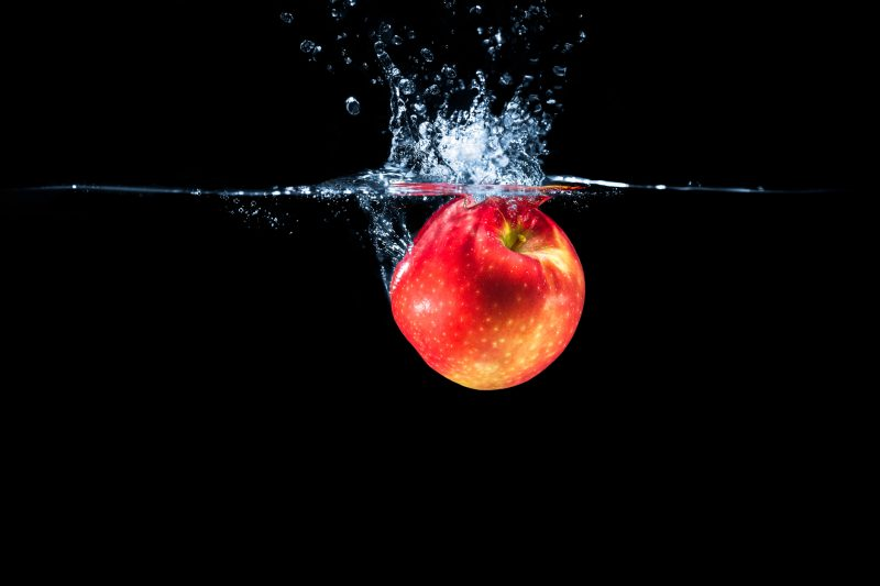 Red apple and water splash isolated on black background